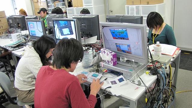 Jovem testa um dos games de DS com uma camera ligada em cima dele para registrar os erros e seus hábitos de jogador